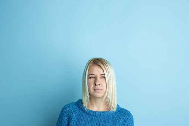 Portrait de jeune femme caucasienne a l'air rêveur, mignon et heureux. penser, se demander, rêver sur fond bleu studio. copyspace pour votre annonce. concept d'avenir, cible, rêves, visualisation.