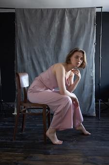 Portrait de jeune femme caucasienne aux cheveux courts posant en costume rose, assis sur une chaise en face de fond de tissu. essais sur modèle de jolie fille en chemisier. jolies poses féminines et sourires