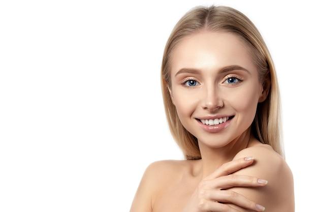 Portrait de jeune femme caucasienne belle toucher son épaule isolée. concept de peau douce, de soins de la peau ou de cosmétologie