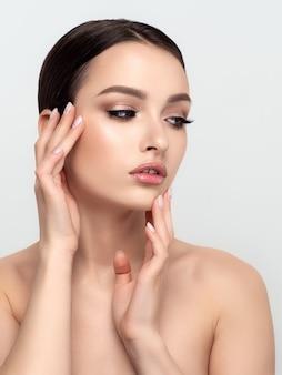 Portrait de jeune femme caucasienne belle toucher son visage isolé. nettoyage de la peau, soins de la peau, concept de cosmétologie