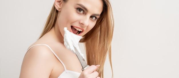 Portrait de jeune femme caucasienne avec couteau et mousse à raser regardant la caméra sur fond blanc