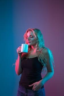 Portrait de jeune femme caucasienne sur fond dégradé en néon. beau modèle féminin au look inhabituel. concept d'émotions humaines, expression faciale, ventes, publicité. boire du café ou du thé.