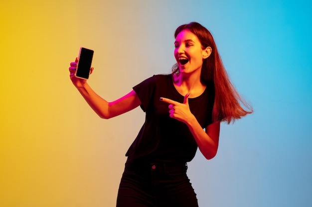 Portrait de jeune femme caucasienne sur fond de studio dégradé bleu-jaune en néon. concept de jeunesse, émotions humaines, expression faciale, ventes, publicité. beau modèle brune.