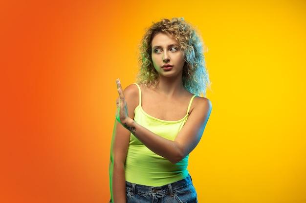 Portrait de jeune femme caucasienne sur fond de studio dégradé en néon