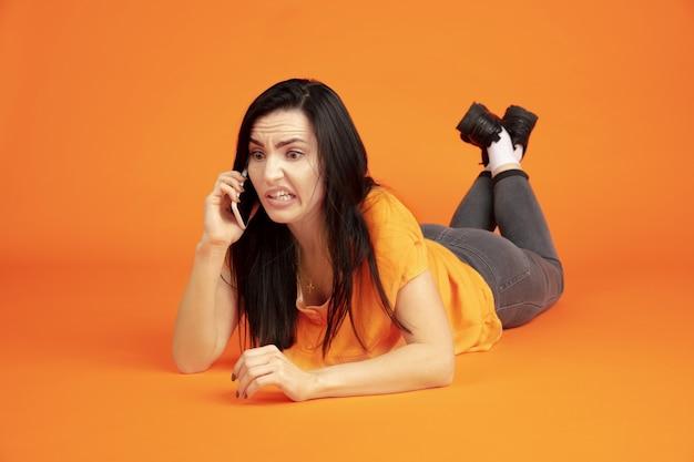 Portrait de jeune femme caucasienne sur fond de studio orange. beau modèle femme brune en chemise. concept d'émotions humaines, expression faciale, ventes, publicité. copyspace. parler au téléphone.