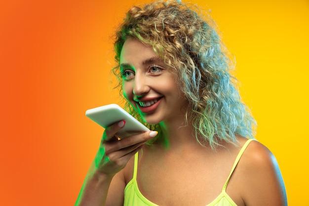 Portrait de jeune femme caucasienne isolée sur fond de studio dégradé en néon