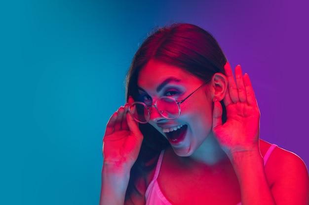 Portrait d'une jeune femme caucasienne isolée sur fond violet-bleu dégradé en néon, cinéma, visionnage de films