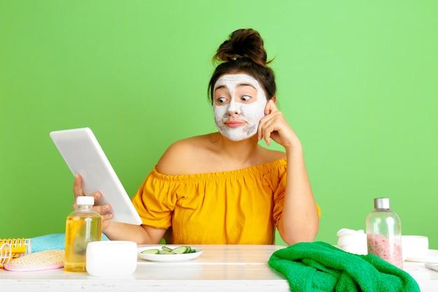 Portrait de jeune femme caucasienne en journée de beauté, routine de soins de la peau et des cheveux. modèle féminin faisant selfie, vlog ou appel vidéo tout en appliquant un masque facial. concept de soins personnels, de beauté naturelle et de cosmétiques.