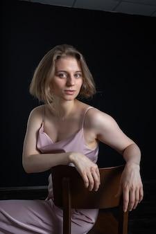 Portrait de jeune femme caucasienne pensive aux cheveux courts posant en costume rose, assis sur une chaise devant le noir. essais sur modèle de jolie dame en chemisier, pantalon. poses féminines attrayantes