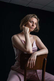 Portrait de jeune femme caucasienne pensive aux cheveux courts posant en costume rose, assis sur une chaise en face de noir