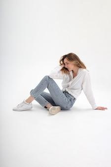 Portrait de jeune femme caucasienne posant en chemise et jeans, assis sur le sol du studio blanc