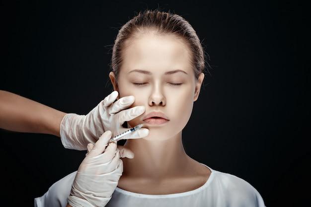 Portrait de jeune femme caucasienne reçoit une injection cosmétique