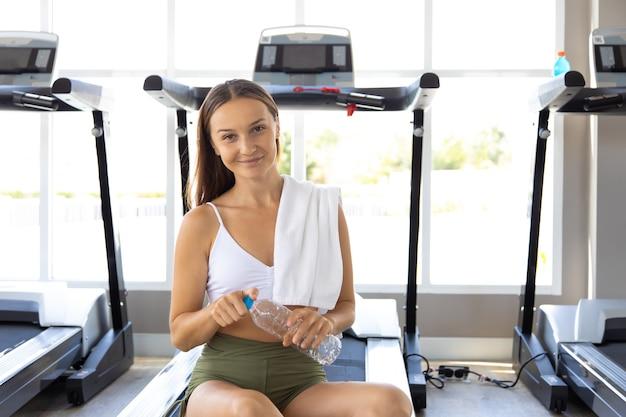 Portrait de jeune femme caucasienne en tenue de sport tenant une bouteille d'eau et boire assis sur un tapis roulant à la salle de fitness. concepts de mode de vie sain et de sport.