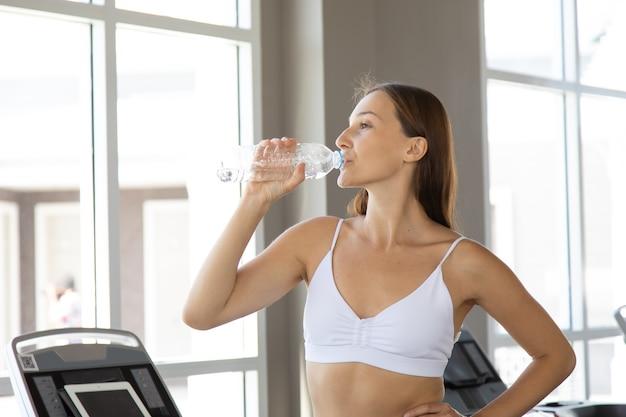 Portrait de jeune femme caucasienne en tenue de sport tenant une bouteille d'eau et de boire à la salle de fitness. concepts de mode de vie sain et de sport.