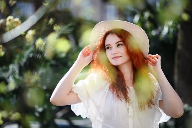 Portrait de jeune femme avec chapeau debout à l'extérieur de la ville en été.