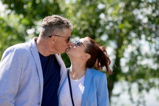 Portrait de jeune femme chaude et sexy appréciant le baiser de son mari âgé