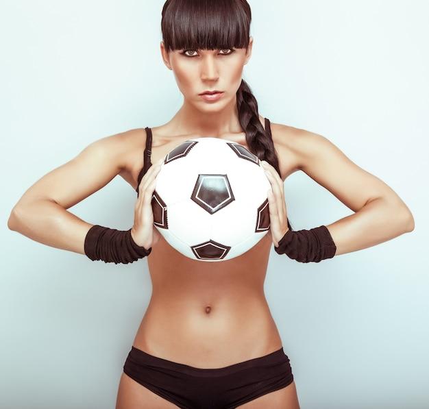 Portrait d'une jeune femme chaude tenant un ballon de football