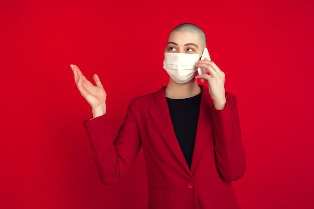 Portrait de jeune femme chauve caucasienne avec masque facial sur mur rouge