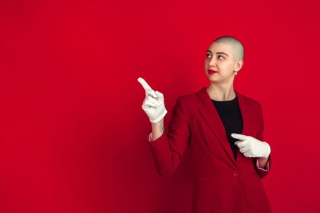 Portrait de jeune femme chauve caucasienne sur mur rouge