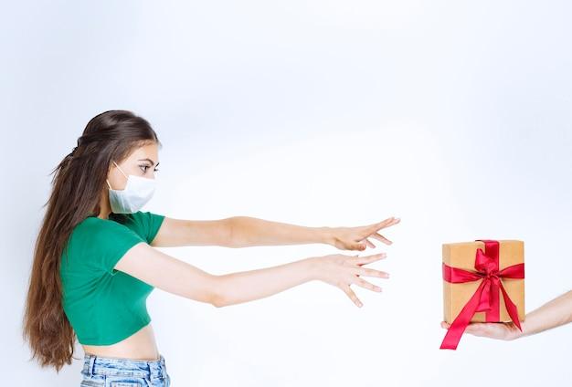 Portrait de jeune femme en chemise verte essayant d'atteindre son cadeau.