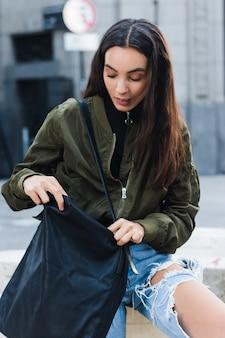 Portrait d'une jeune femme cherchant dans son sac