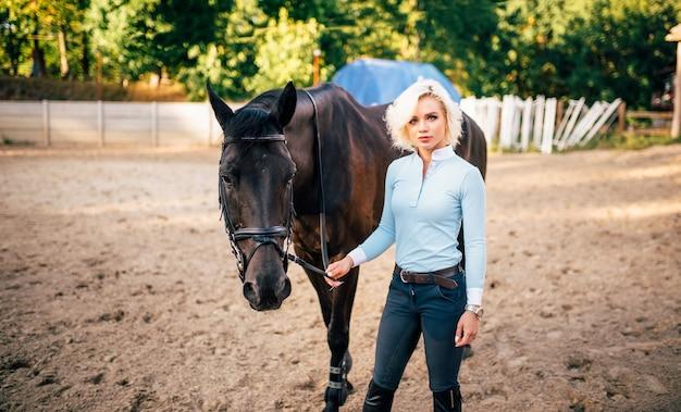 Portrait de jeune femme avec cheval brun. sport équestre, jolie dame et bel étalon