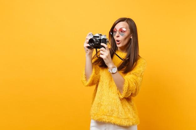 Portrait de jeune femme choquée à lunettes coeur prenant des photos sur un appareil photo vintage rétro isolé sur fond jaune vif. les gens émotions sincères, concept de style de vie. espace publicitaire.