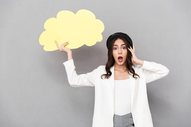 Portrait d'une jeune femme choquée portant béret debout isolé sur fond gris, montrant une bulle de dialogue vide