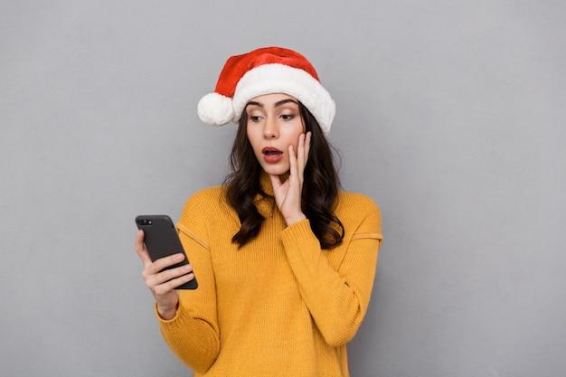 Portrait d'une jeune femme choquée portant chapeau de père noël rouge debout isolé sur fond gris, à l'aide de téléphone mobile