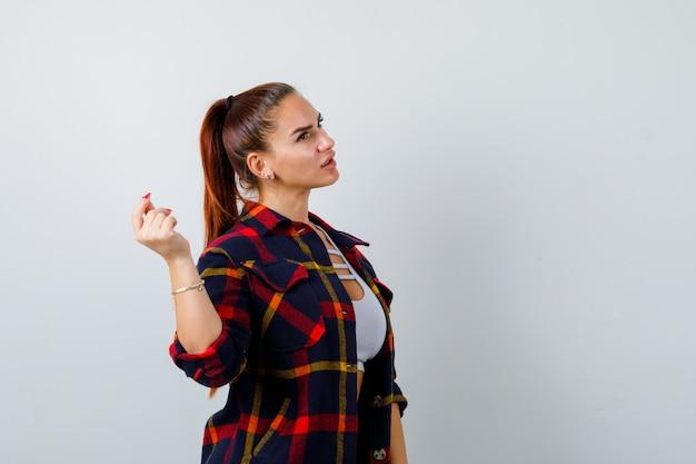 Portrait de jeune femme cliquant sur les doigts tout en générant une idée dans un haut court, une chemise à carreaux, un pantalon et une vue de face intelligente