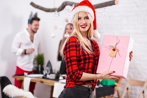 Portrait d'une jeune femme avec un coffret rose à la maison au premier plan belle blonde dans un père noël ...