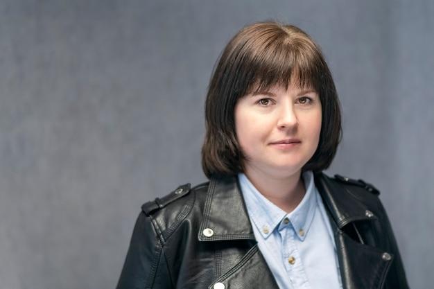 Portrait de jeune femme confiante avec coupe de cheveux bob en blouson de cuir. fille brune avec une forme de visage rond. femme d'âge moyen