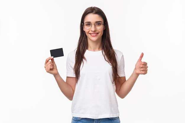 Portrait de jeune femme confiante et heureuse, souriante en t-shirt, lunettes, montrer le pouce en l'air et hocher la tête