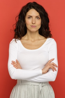 Portrait d'une jeune femme confiante avec un léger sourire et les mains croisées debout sur le mur rouge du studio