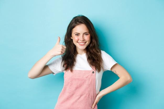 Portrait d'une jeune femme confiante et positive montre le pouce vers le haut, dit oui, donne la permission, approuve et accepte quelque chose de bien, loue un bon choix, debout sur fond bleu.