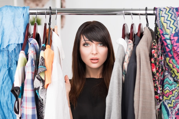 Portrait de jeune femme confuse devant une armoire pleine de vêtements