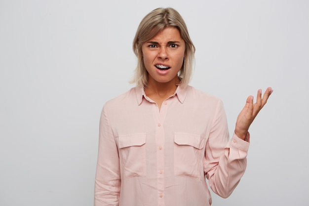 Portrait de jeune femme confuse malheureuse aux cheveux blonds et bretelles sur les dents porte chemise rose