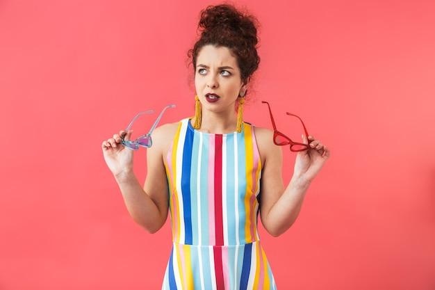 Portrait d'une jeune femme confuse portant une robe isolée sur fond rouge, choisissant des lunettes de soleil