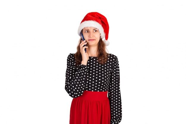 Portrait de jeune femme confuse en robe parler sur son téléphone. fille émotive au chapeau de noël père noël isolé