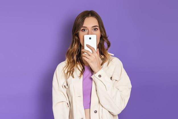Portrait d'une jeune femme confuse surprise isolée sur fond lilas