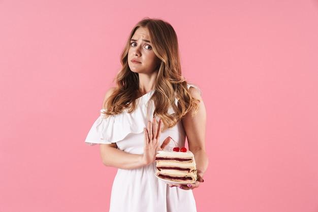 Portrait de jeune femme confuse vêtue d'une robe blanche faisant un geste d'arrêt et tenant un morceau de gâteau isolé sur un mur rose