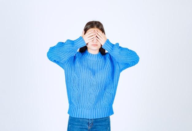 Portrait d'une jeune femme coning ses yeux avec ses mains.