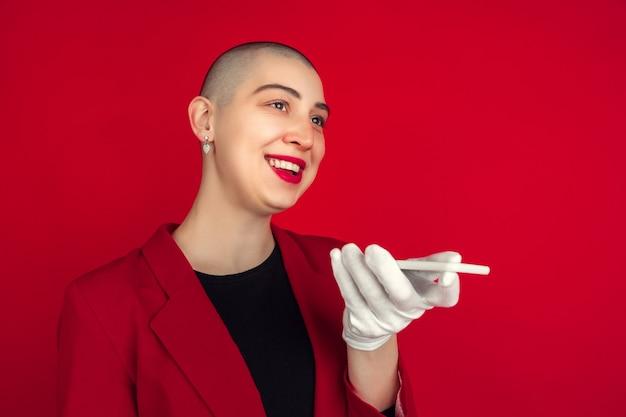 Portrait de jeune femme en costume rouge avec téléphone isolé sur studio rouge
