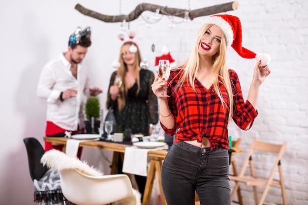 Portrait d'une jeune femme avec une coupe de champagne à la maison au premier plan belle blonde dans un ...