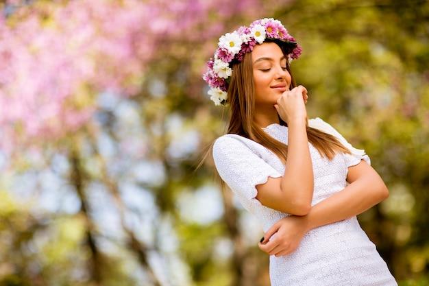 Portrait de jeune femme avec une couronne de fleurs fraîches sur la tête