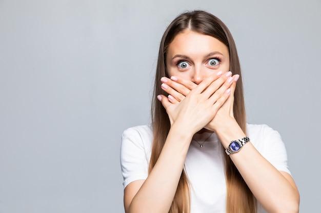 Portrait de jeune femme couvrant la bouche avec la main isolée