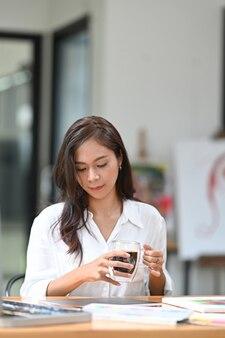 Portrait jeune femme créative tenant une tasse de café et assise dans son atelier.