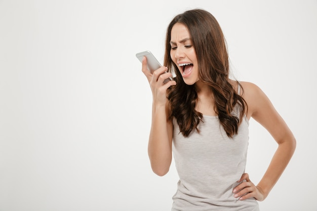 Portrait de jeune femme criant dans le téléphone mobile, étant ennuyé et en colère contre le blanc
