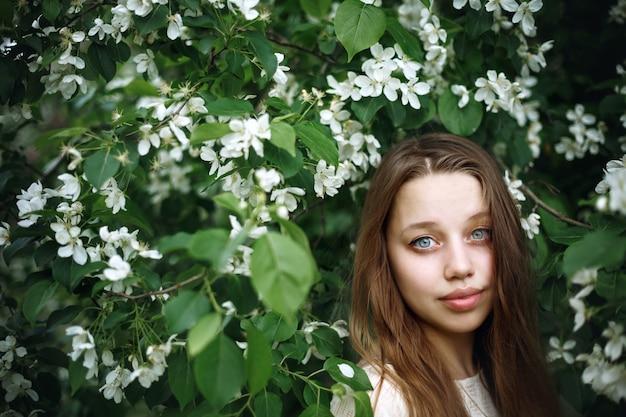 Portrait de jeune femme dans l'arbre de printemps en fleurs, beauté naturelle