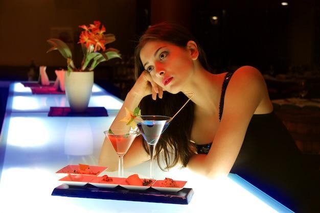 Portrait d'une jeune femme dans un bar à cocktails